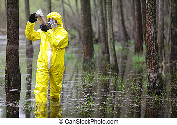 technician checking sample of water - fully protected in...