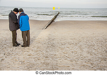 Two man on the sandy beach - Kolobrzeg, Poland.