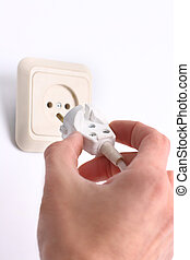 Hand inserting green electrical plug