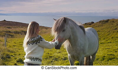 petting white horse - young blonde woman strokes an...