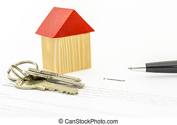Mortgage contract - Closeup of wooden toy house and keys on...