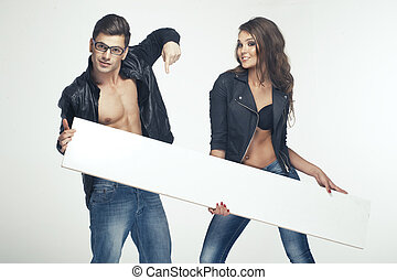 Fashionable happy pretty couple holding white board