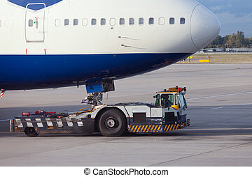 Aircraft tug towing big airliner to dock position - Large...