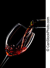 Red wine poured into a glass on black background