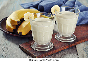 Banana smoothie in glass with fresh fruits on wooden...