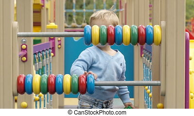 Little boy playing with an abacus with colourful rings on...