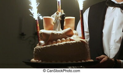 Wedding cake with fireworks - Waiter holding a wedding cake...