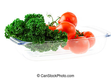 tomatoes and greens with water drops in a glass