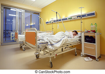 sad middle-aged woman lying in hospital - Real people in...