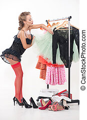 Sexy woman standing in front of a rack of clothes