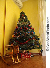 Christmas tree with wooden rocking horse behind
