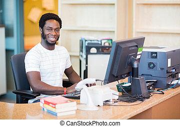 bibliotecário, macho, trabalhando, escrivaninha