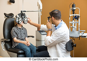 Optometrist Examining Preadolescent Boys Eyes - Mid adult...