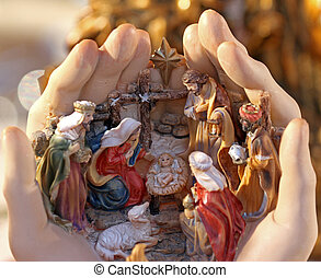 hand holding the crib with statuettes of the Nativity at...