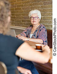 Senior Woman With Friend In Coffee shop