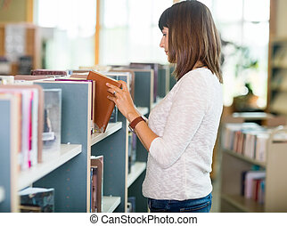 Student Choosing Book In Bookstore - Side view of young...