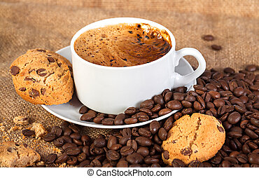 cup with hot coffee and cookies