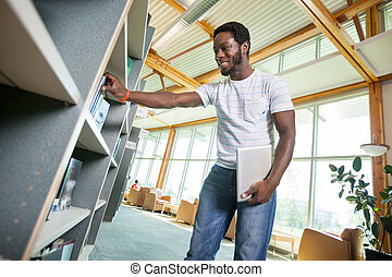 Student Selecting Book In Library - Young male student with...