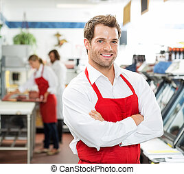 Confident Male Butcher Standing Arms Crossed At Store -...