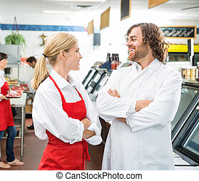Happy Butchers Looking At Each Other In Store