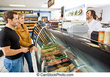 Salesman Attending Customers At Butcher's Shop - Smiling mid...
