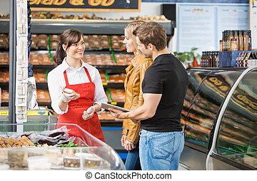 vendedora, Ayudar, pareja, en, compra, carne