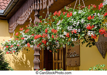 Colourful flower baskets hanging on a porch - Row of several...