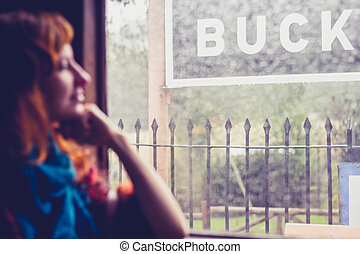 Woman by window in old train carriage at station
