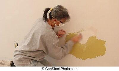 woman sanding a wall - woman hand sanding a wall to prepare...