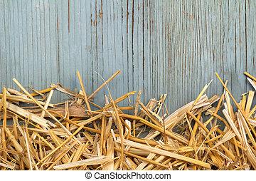 hay against an old blue wooden wall