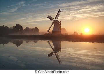 sunrise behind Dutch windmill - misty sunrise behind Dutch...