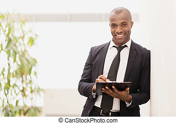 Businessman with note pad Cheerful young African businessman...