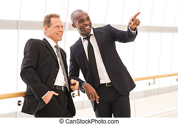 Business people. Two cheerful business men standing close to each other while one of them pointing away and smiling