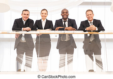Business team. Low angle view of four confident business people standing close to each other and smiling at camera