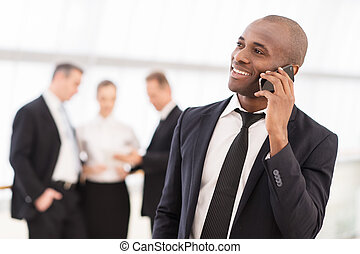 Businessman on the phone. Cheerful young African man in formalwear talking on the mobile phone and smiling while his colleagues standing on background
