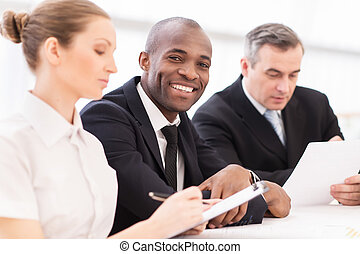 Man on business meeting. Cheerful young African man in...