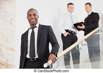 Confident businessman. Cheerful young black man in...