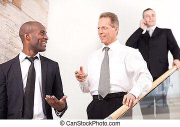 Business people on staircase. Three cheerful man in formalwear moving downstairs while two of them talking to each other and smiling