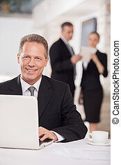 Working on laptop. Cheerful mature man in formalwear sitting at the table and using computer while two colleagues discussing something on background