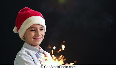 Christmas Magic - Happy lad in Santa hat creating the...