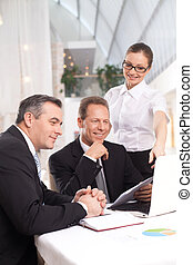 It was a good deal. Two cheerful men in formalwear sitting at the table while woman in white shirt standing close to them and pointing computer monitor