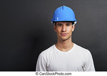 Young construction worker in hard hat on dark background