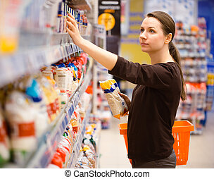 Young woman shopping for cereal, bulk in a grocery...