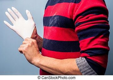 Man putting on latex glove