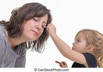 Little girl applying makeup to her mother - Adorable litte...
