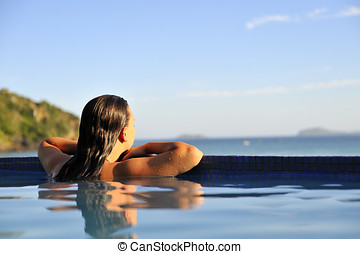 Summer relaxing time - Woman relaxing on a swimming pool...