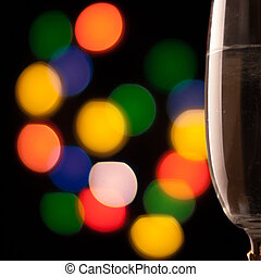 two glasses of champagne toasting against bokeh lights...