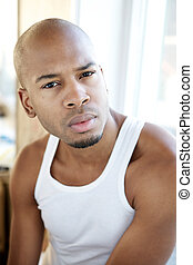 Portrait of a handsome young man sitting alone indoors -...