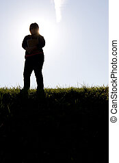 Student Silhouette - A young college student posing with her...