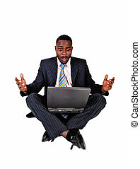 Surprised black man. - A black businessman sitting on the...